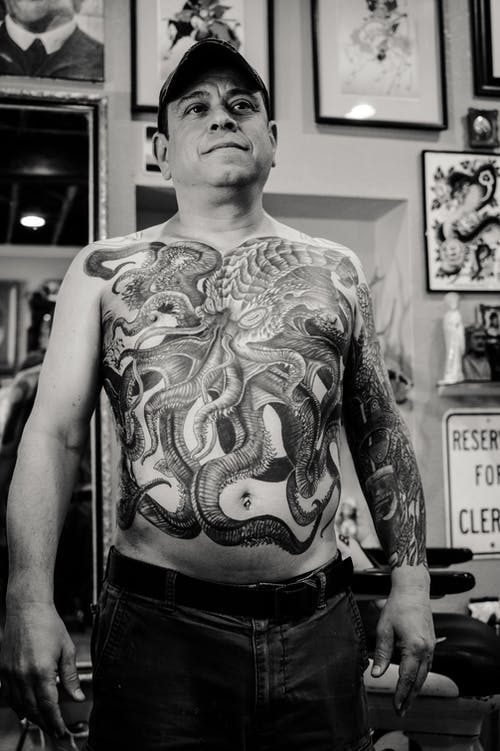 Man Standing and Showing His Body Tattoo