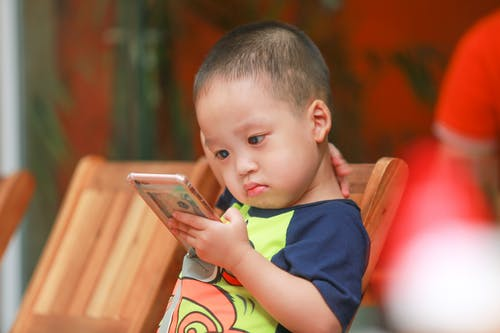 Boy Holding Smartphone Siting on Chair