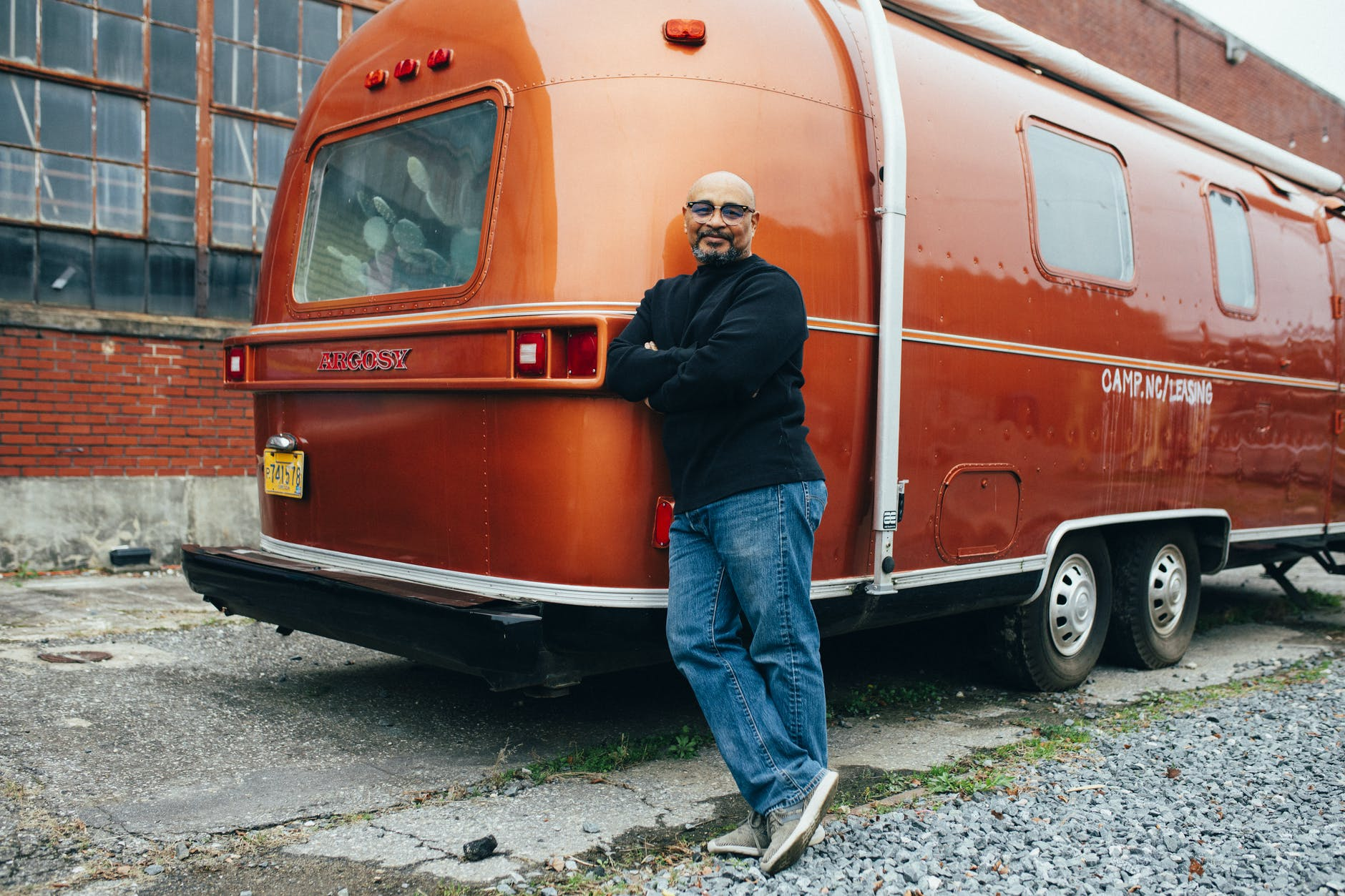 Man leaning beside an orange RV