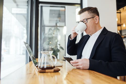 Man Drinking Coffee in Front of His Laptop