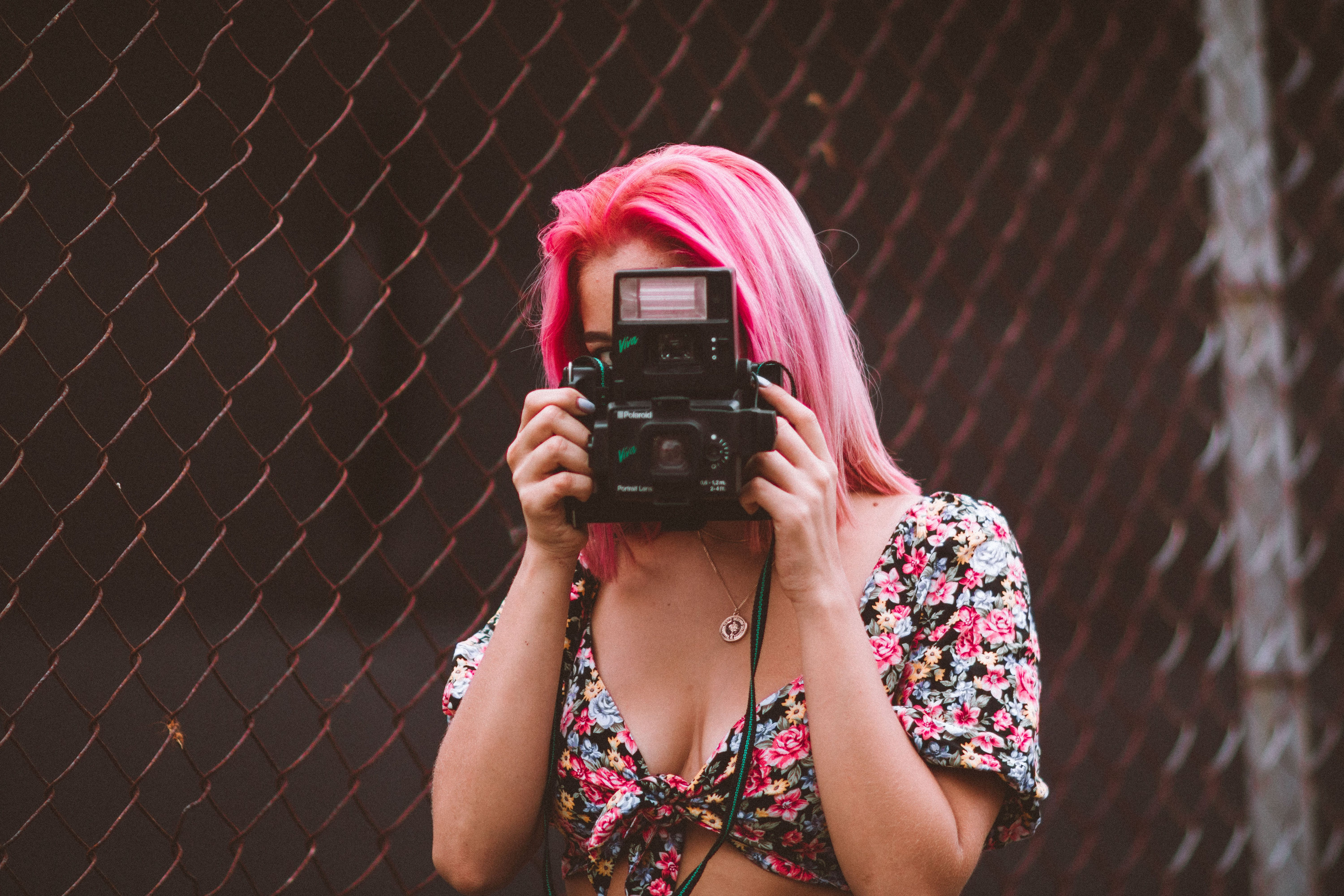 Woman Wearing Pink And Black Floral Top Taking Photo