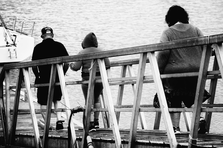 3 Person Walking on Bridge Black and White Photo