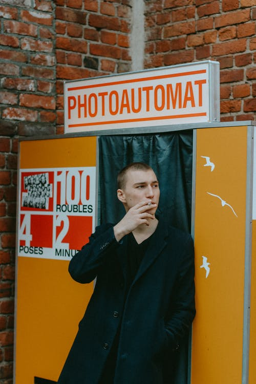Man Smoking In Front Of Photo Booth