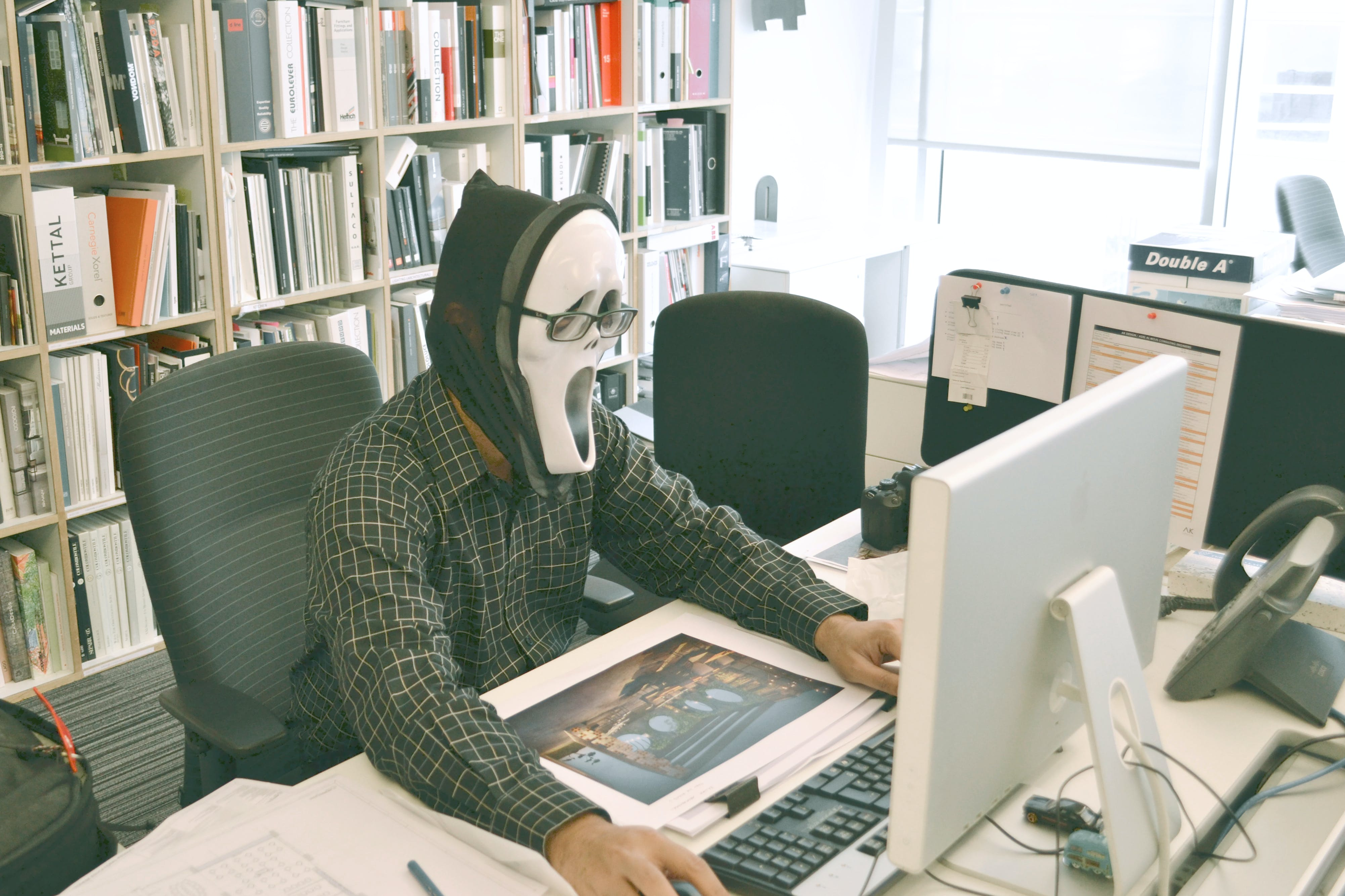 Person Wearing Scream Mask and Black Dress Shirt While Facing Computer Table during Daytime