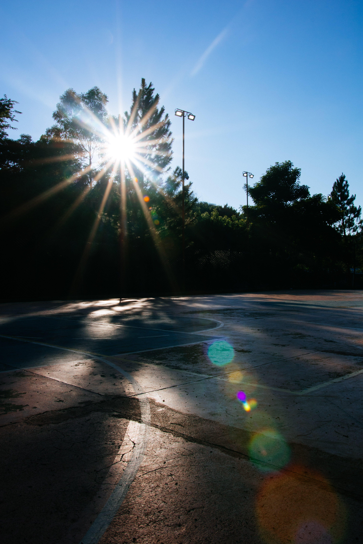 Безкоштовне стокове фото на тему «баскетбольний майданчик, корт, сонце, сонячне світло»