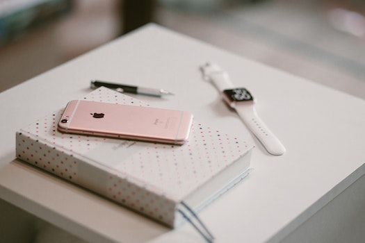 Rose Gold Iphone 6 S on Top of White Covered Book