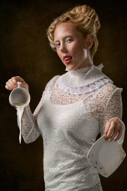 Woman Wearing White Floral Long Sleeve Dress Holding Cup And Saucer