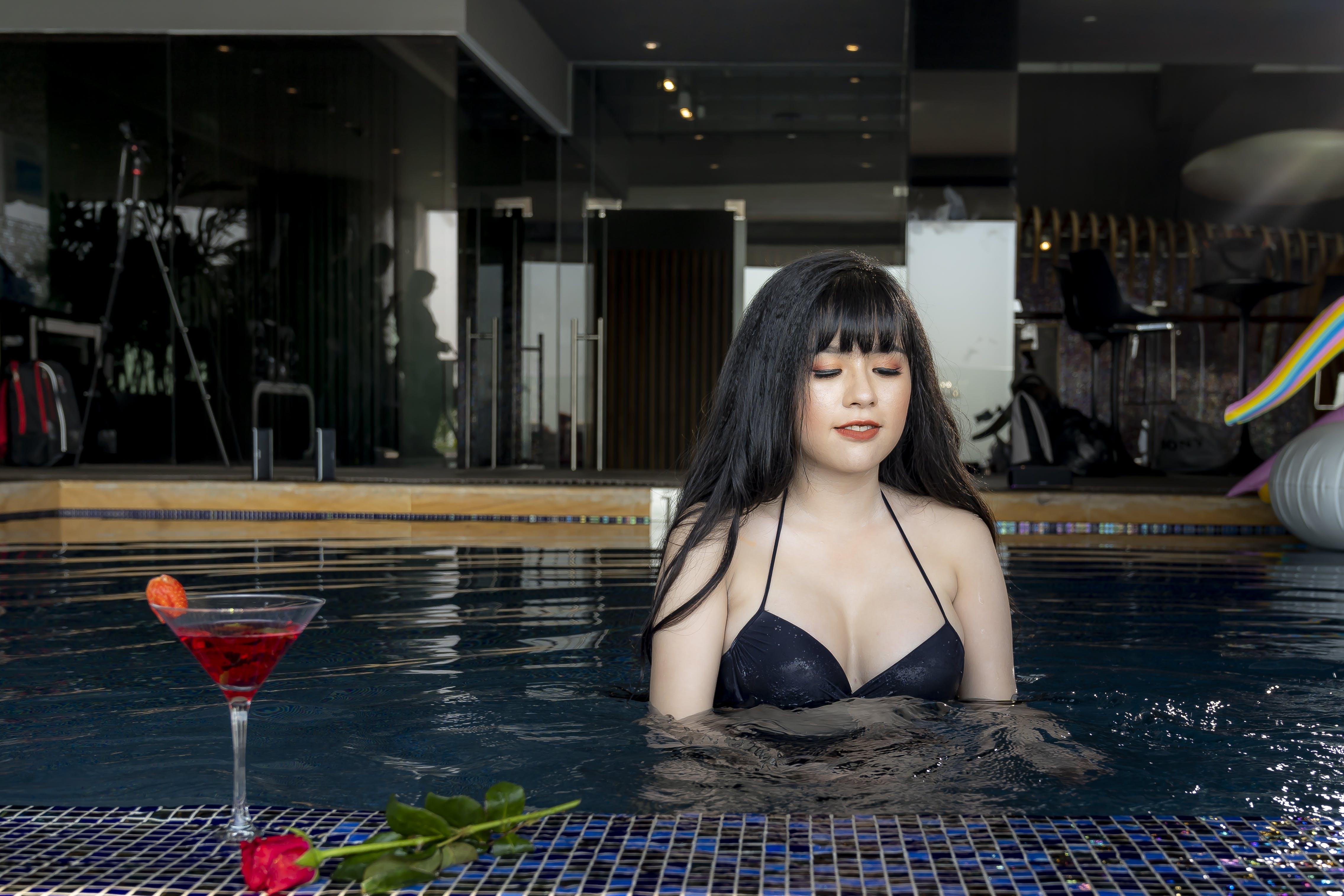 Woman Wearing Black Bikini Top on Swimming Pool Near Glass of Wine and Red Rose Flower