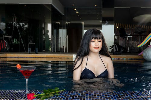Woman Wearing Black Bikini Top on Swimming Pool Near Glass of Wine and Red Rose Flower