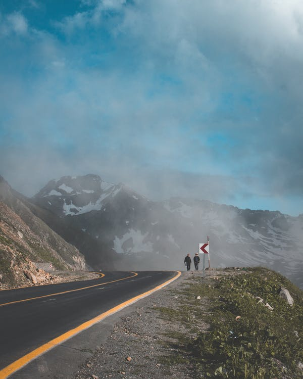 Two Person Walking Beside Road