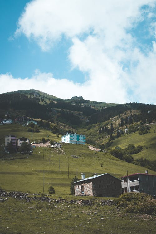 Peaceful scenery of remote village with cozy small cottages located on grassy hills during clear sunny day