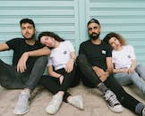 Four Person Sitting on Floor Leaning on Shutter Door