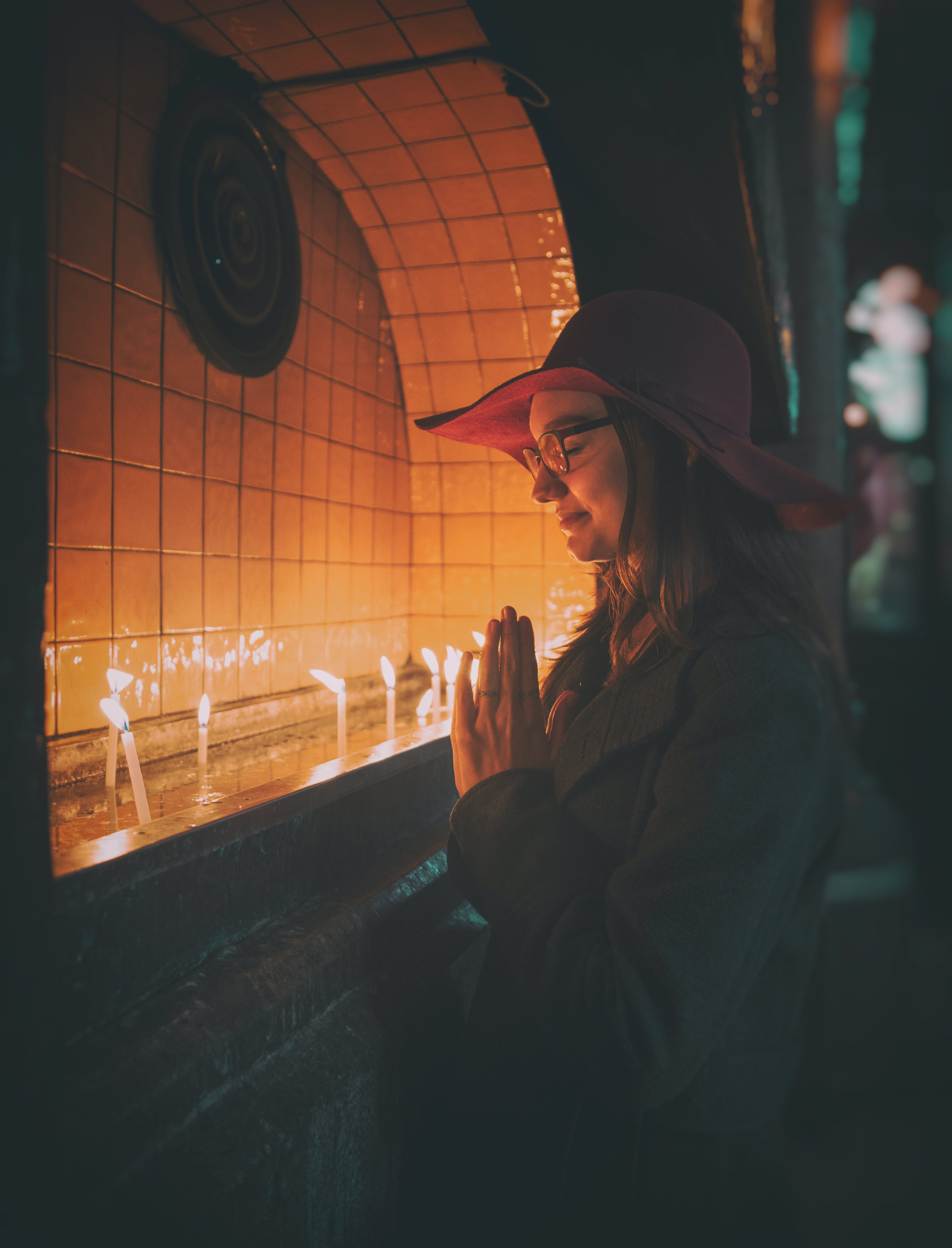Woman Praying In Front of Lit Candles