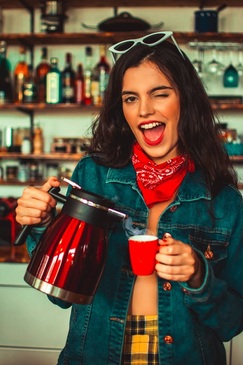 Photo of Winking Woman In Blue Denim Jacket Holding Red Electric Kettle and Cup