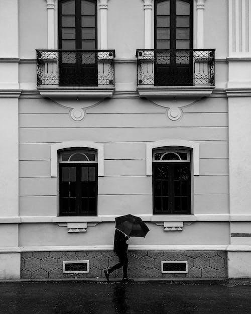 Person Walking Beside Building