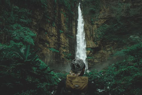Man Standing Near Waterfall