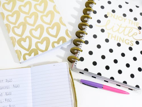 Opened Notebook Beside Pink and Purple Pen and White and Black Polka-dot Notebook