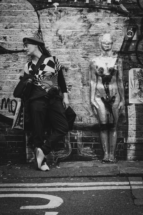 Grayscale Photography Of Woman Standing Beside Human Figure While Looking To Her Right