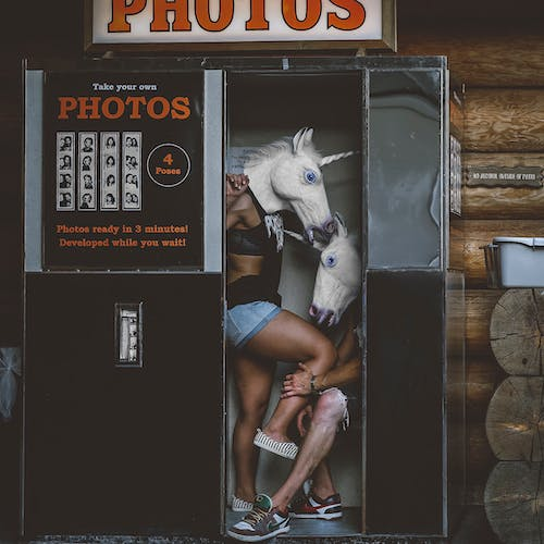 Two Persons With Unicorn Head Costumes in Photo Booth