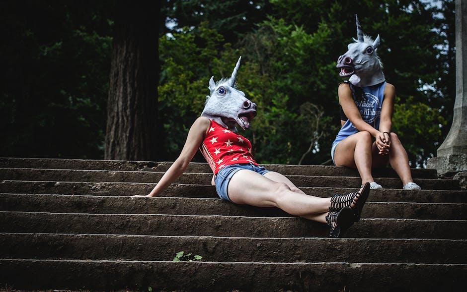 Two women wearing unicorn masks
