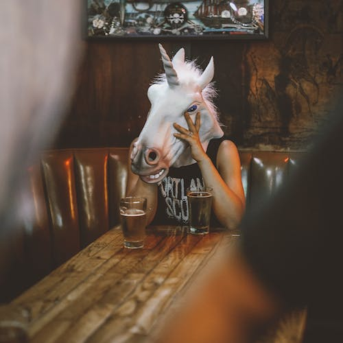 Person With Unicorn Head Sitting Near Table