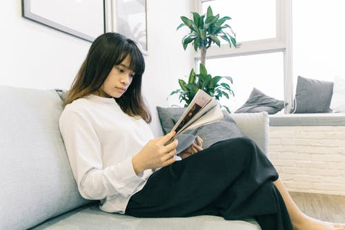 Photo of Woman Reading Magazine While Sitting on Gray Sofa