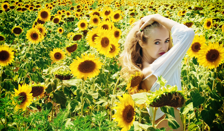 Woman in White Long Sleeve Shirt on Sunflower Field