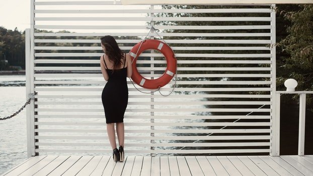 Woman in Black Sheath Dress Beside Swim Ring on Dock