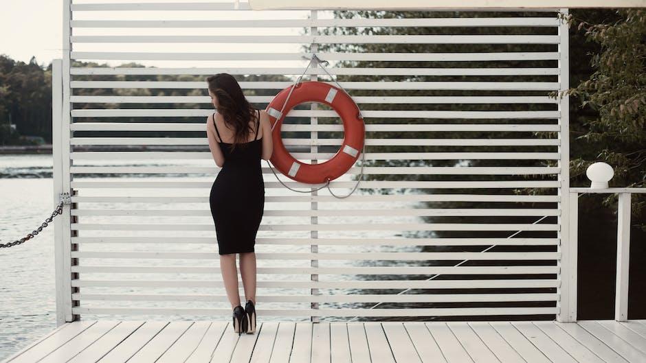 Woman in Black Sheath Dress Beside Swim Ring on Dock