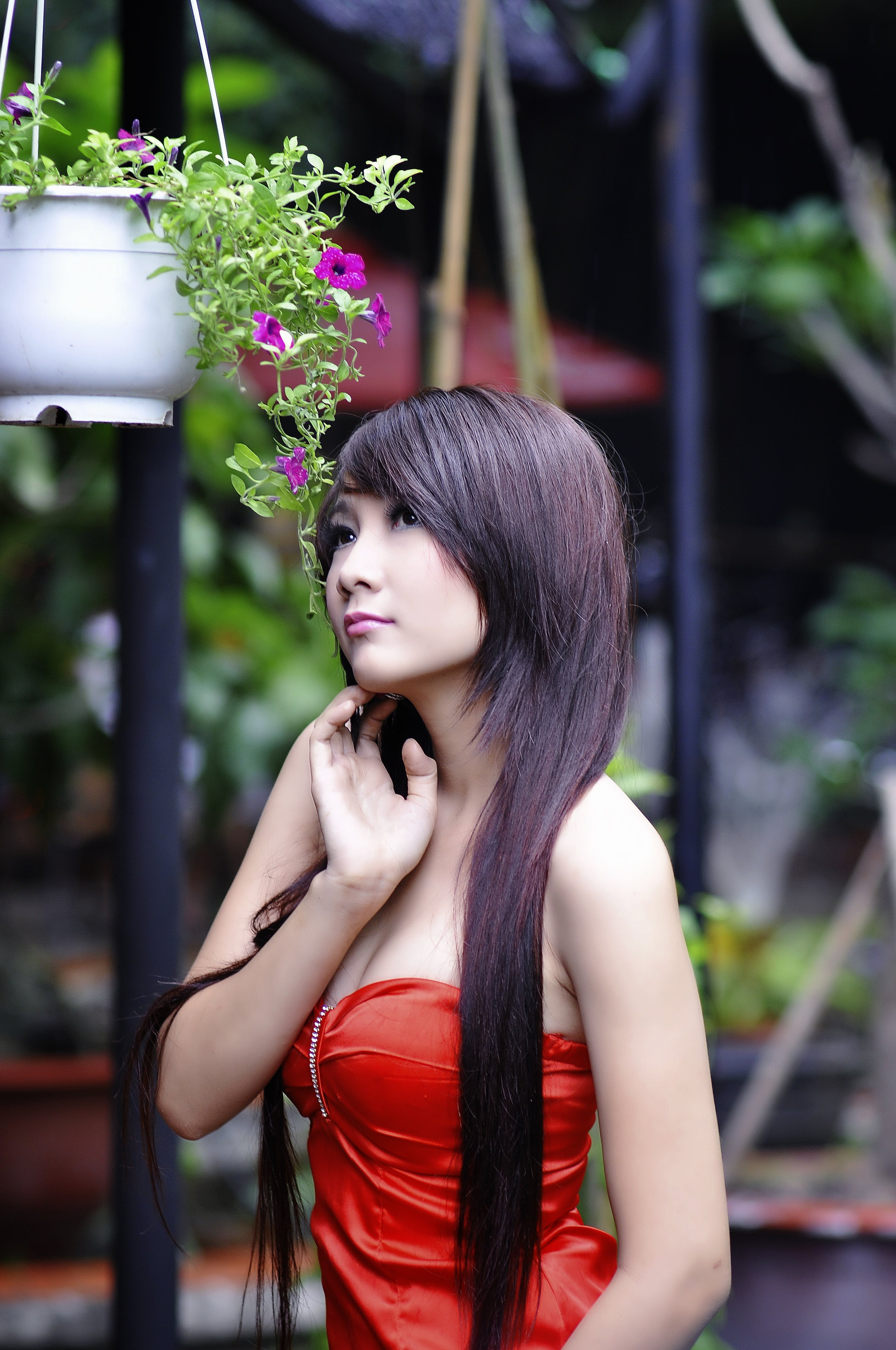 Woman Wearing Red Sweet Heart Neckline Dress Standing Near Hanging Flower Vase