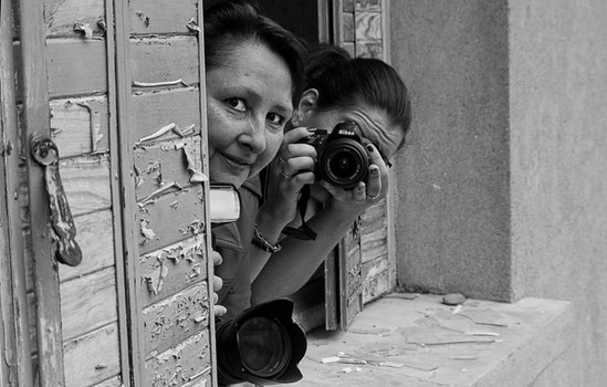 Grayscale Photo of 2 Woman on Window Pane