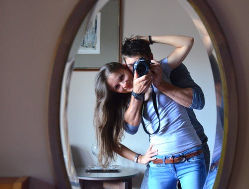 Man and Woman Taking Photo in Front of Mirror