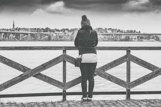 Woman Near Wooden Railing and Body of Water Grayscale Photo