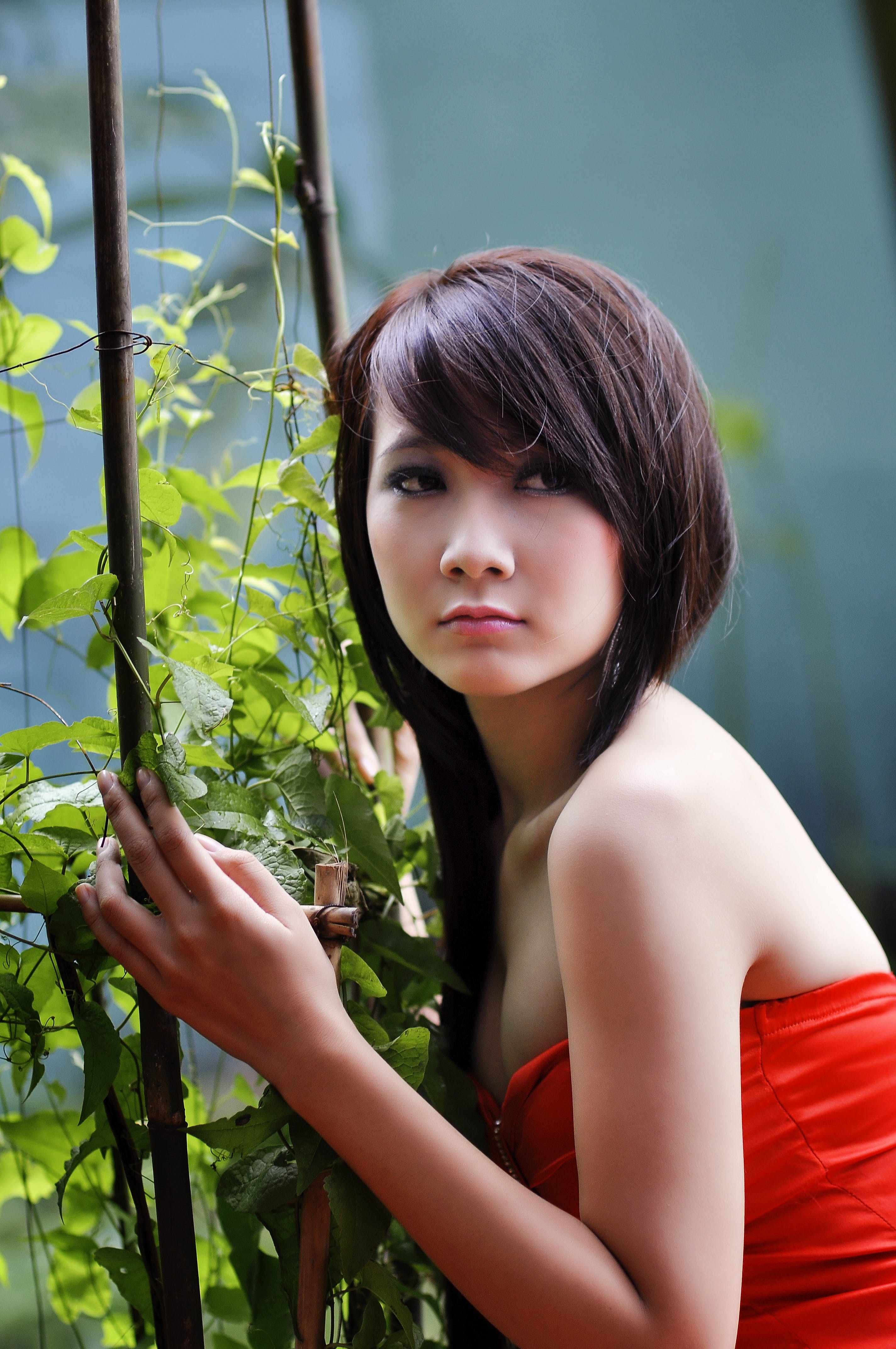 Woman Wearing Red Strapless Top Beside Green Leafed Plants
