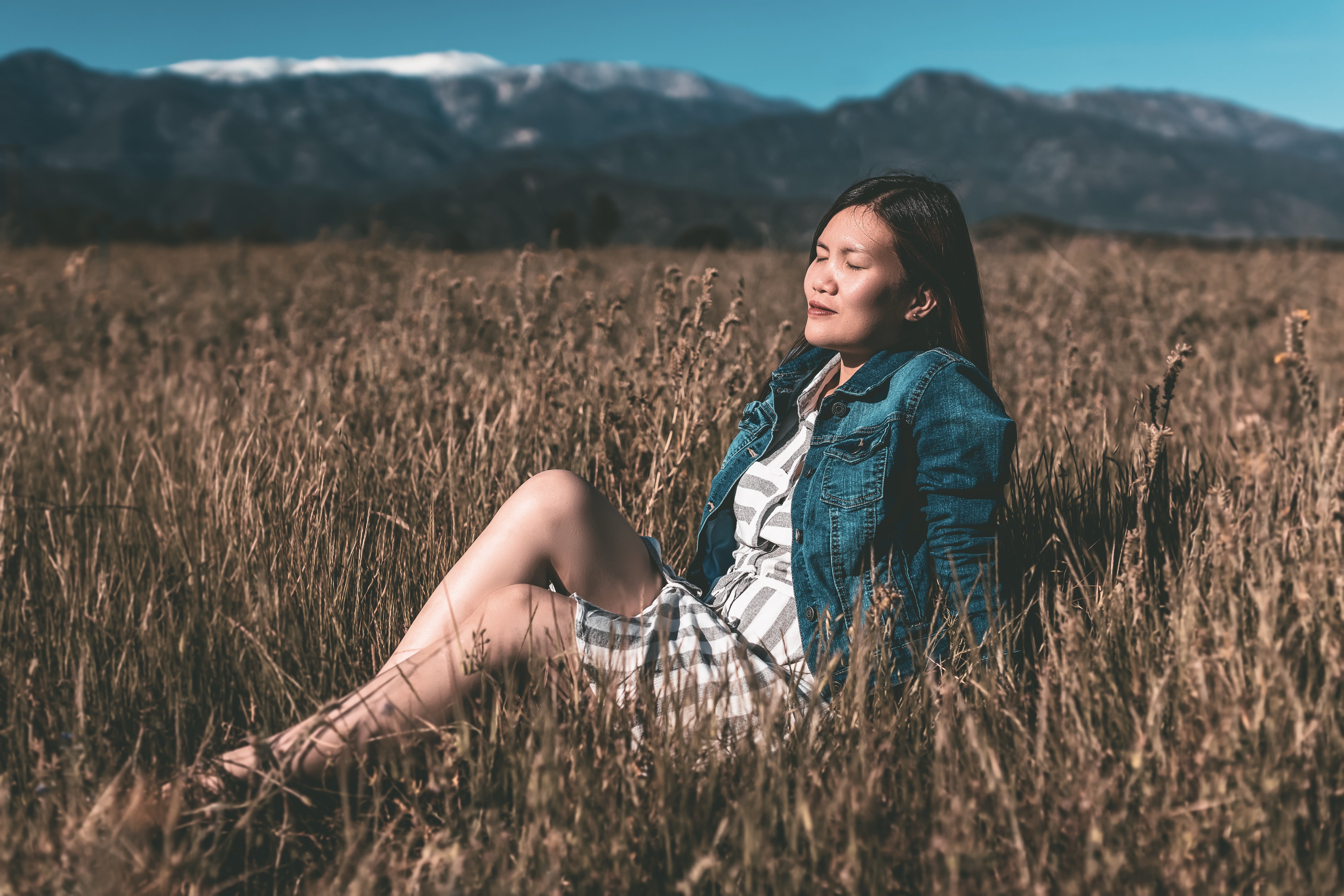 Woman Sitting on Brown Dry Grass Field