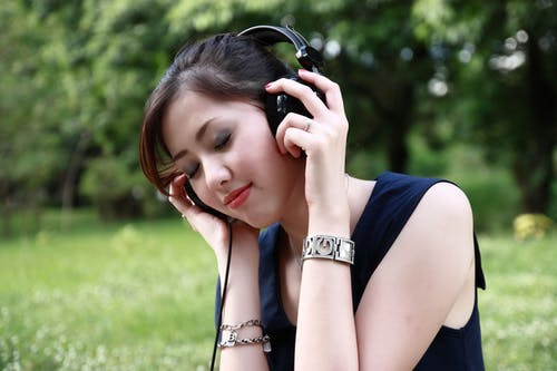 Woman Holding and Wearing Black Corded Headphones Outdoors