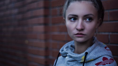 Macro Shot of Woman in Gray Adidas Pull over Hoodie Near Brick Wall