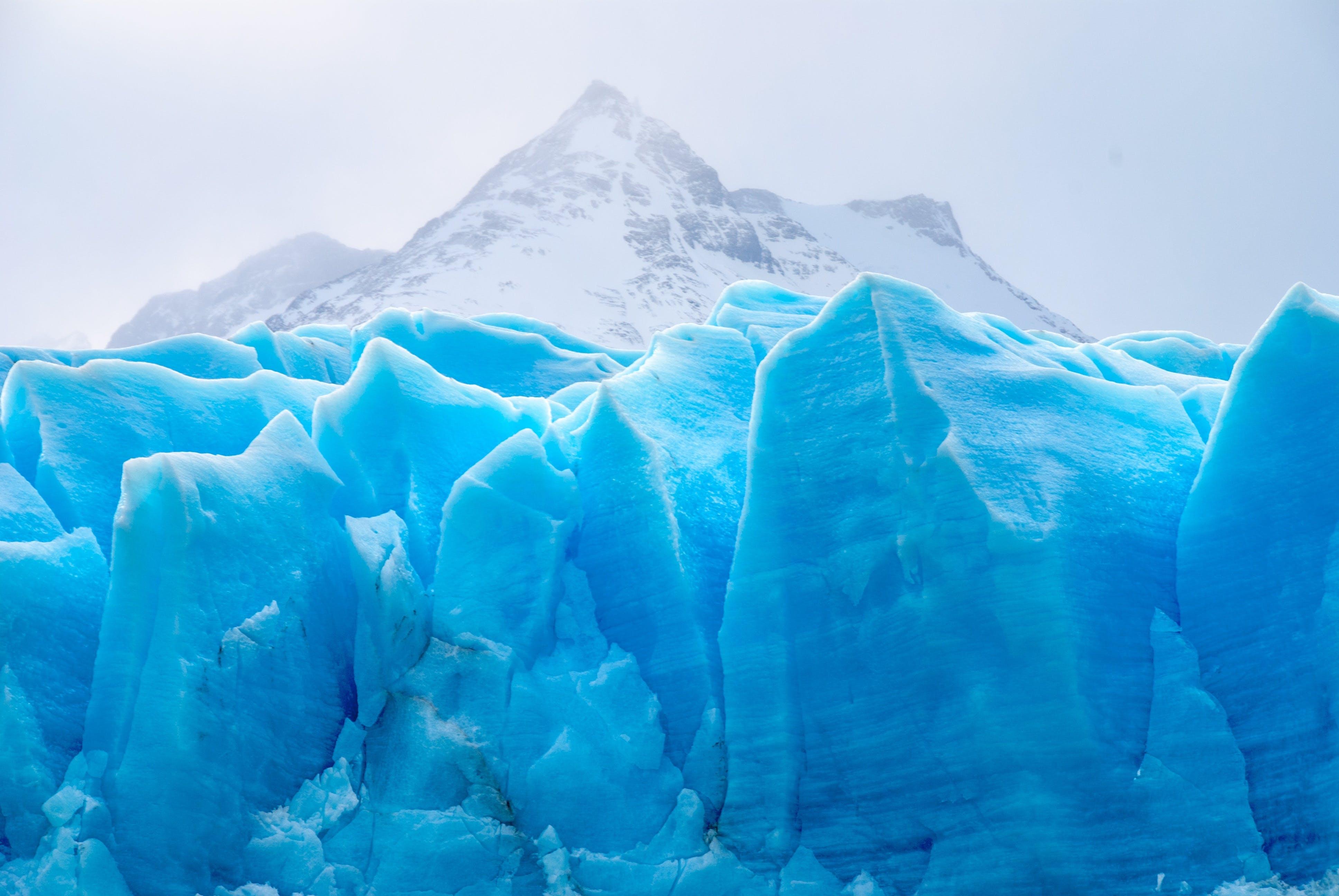 Blue Icebergs Under Cloudy Sky