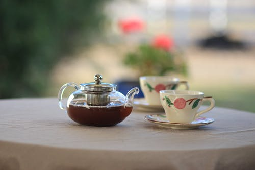 Clear Glass Teapot Near Teacups on Table Selective Focus Photography