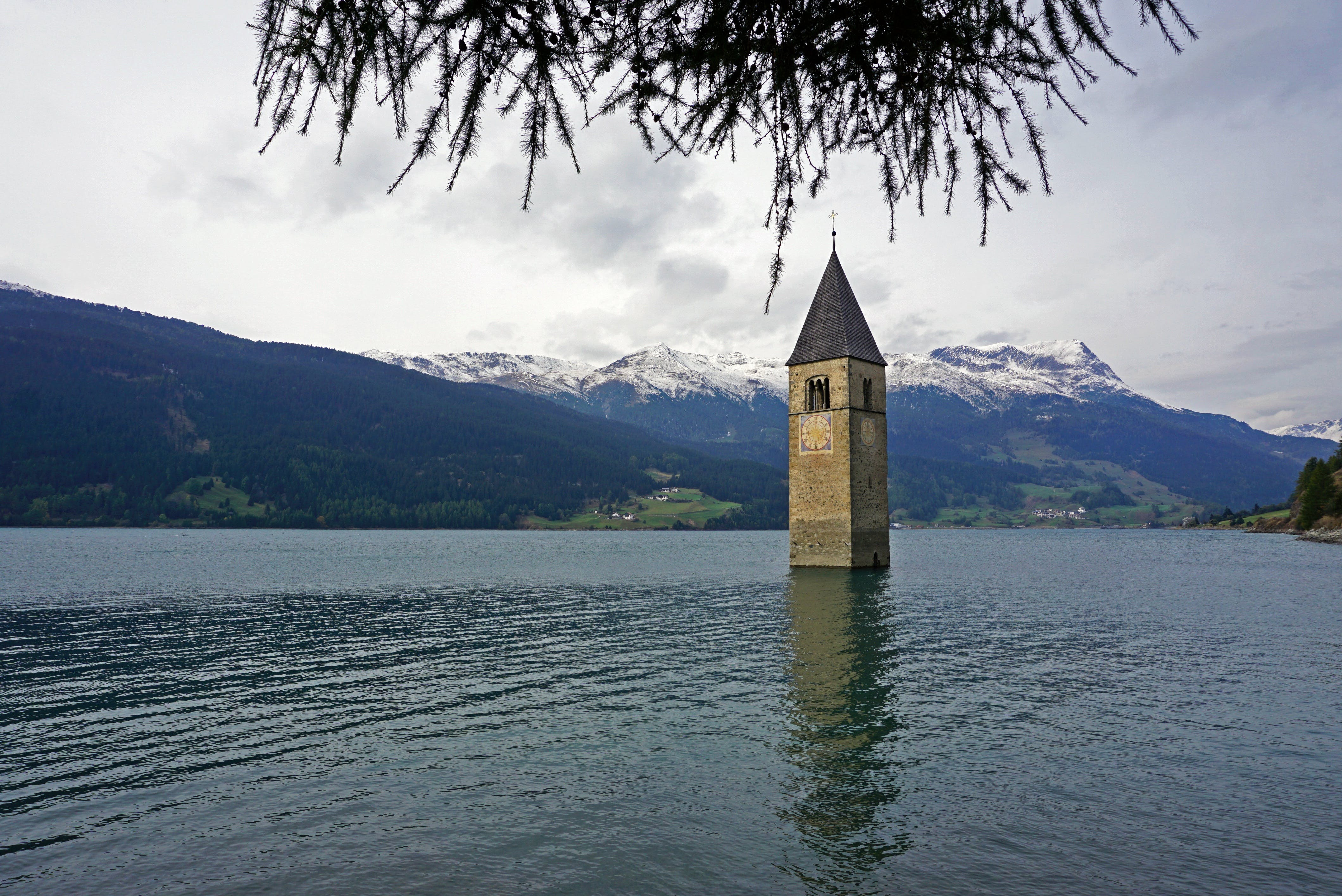 Gray Concrete Tower on Body of Water Under White Skies