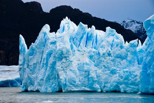 Ice Burg Floating on Water during Daytime