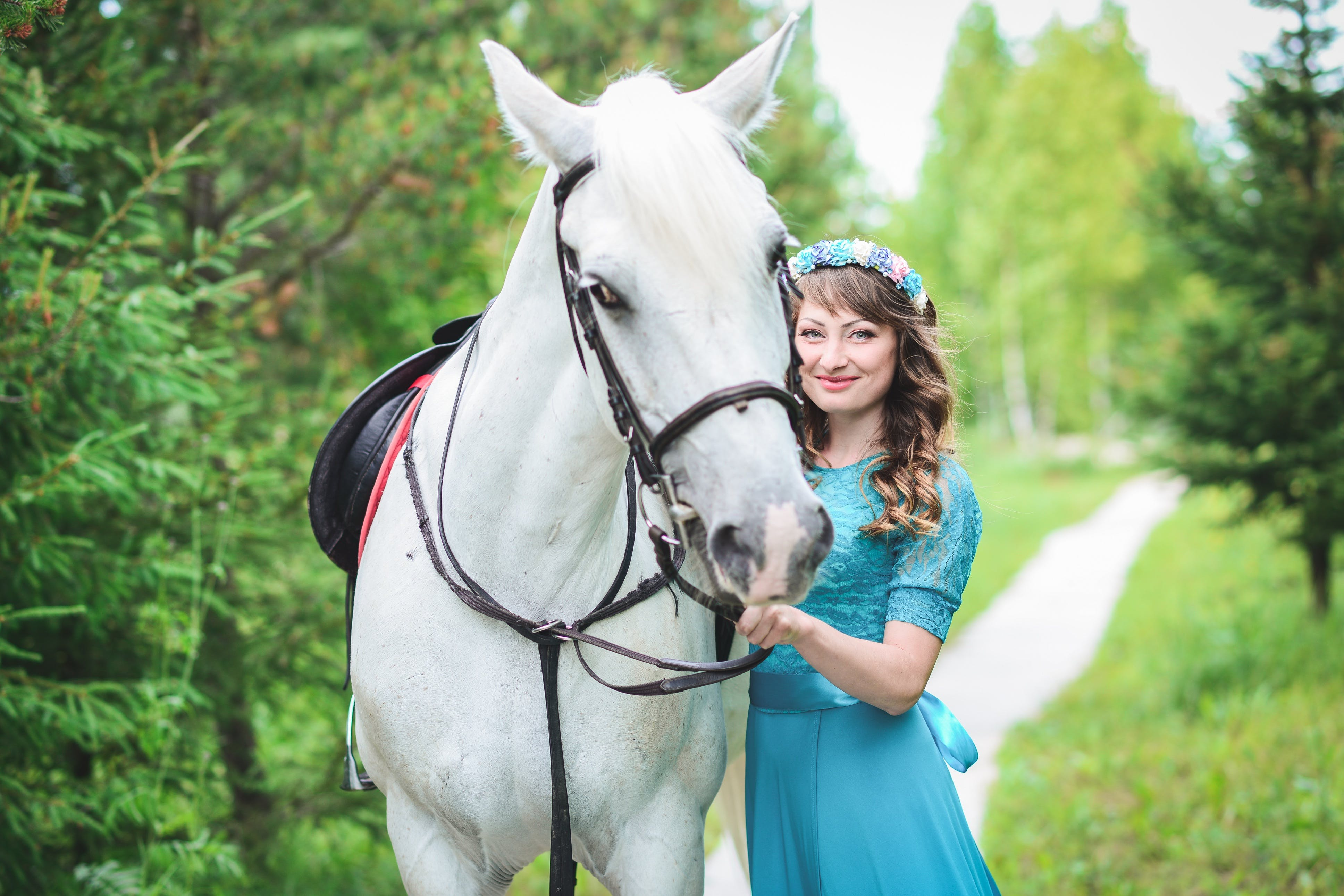Smiling Woman in Blue Dress Standing Beside White Horse