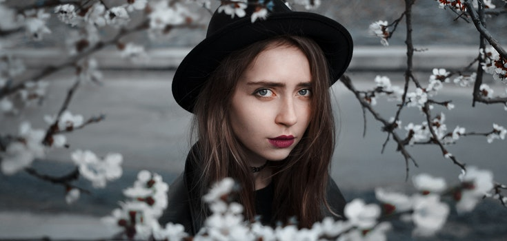 Woman Wearing Black Hat and Dress With Red Lipstick Near White Flowers Selective Focus Photography