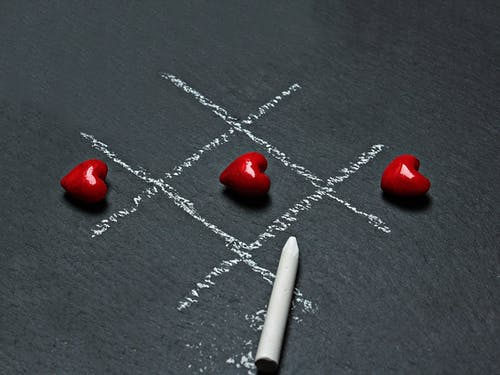 Chalk Drawn Tic-tac-toe With Three Lined-up Heart