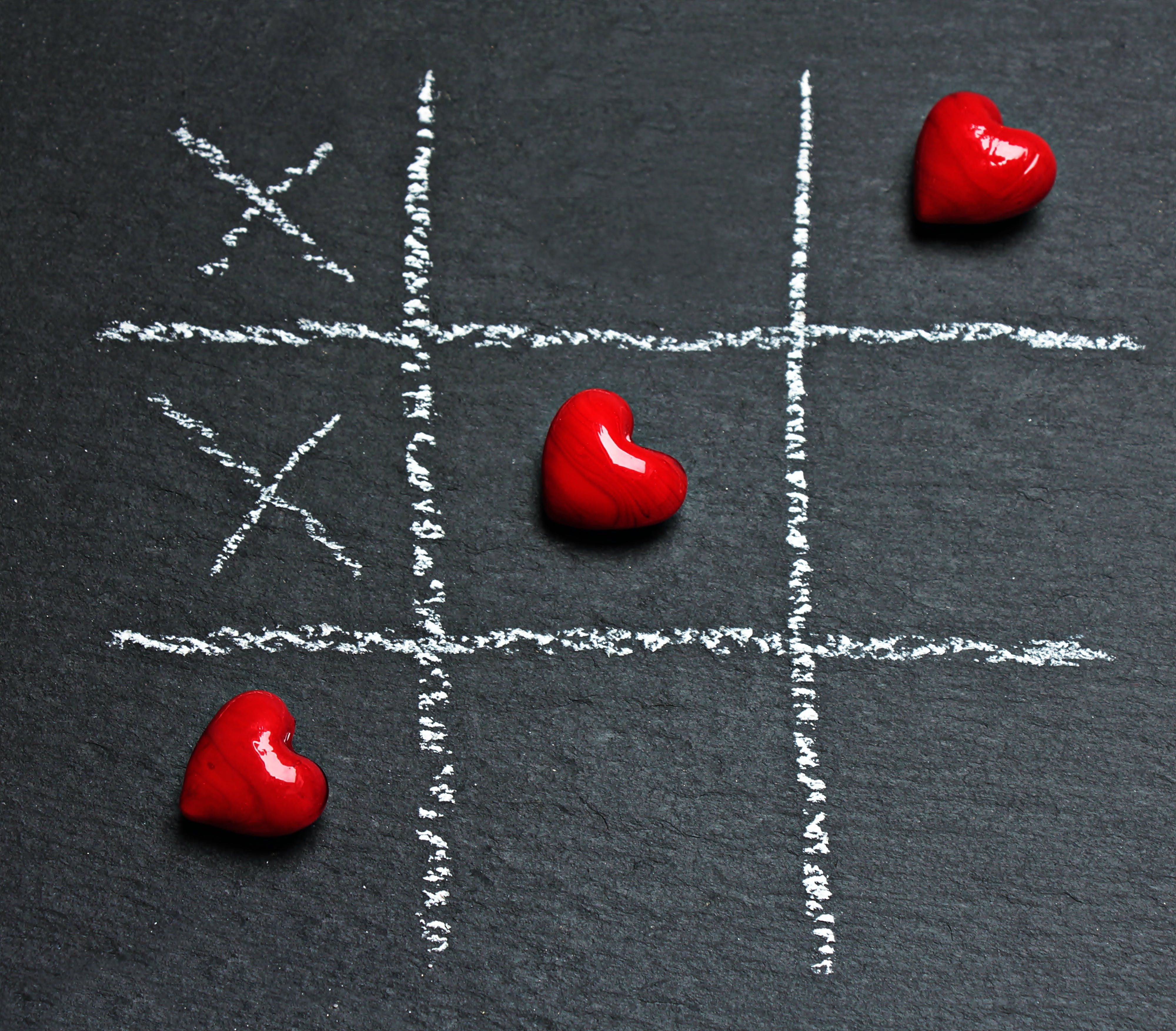 Three Heart-shaped Red Stones Placed on Tic-tac-toe Game Bord