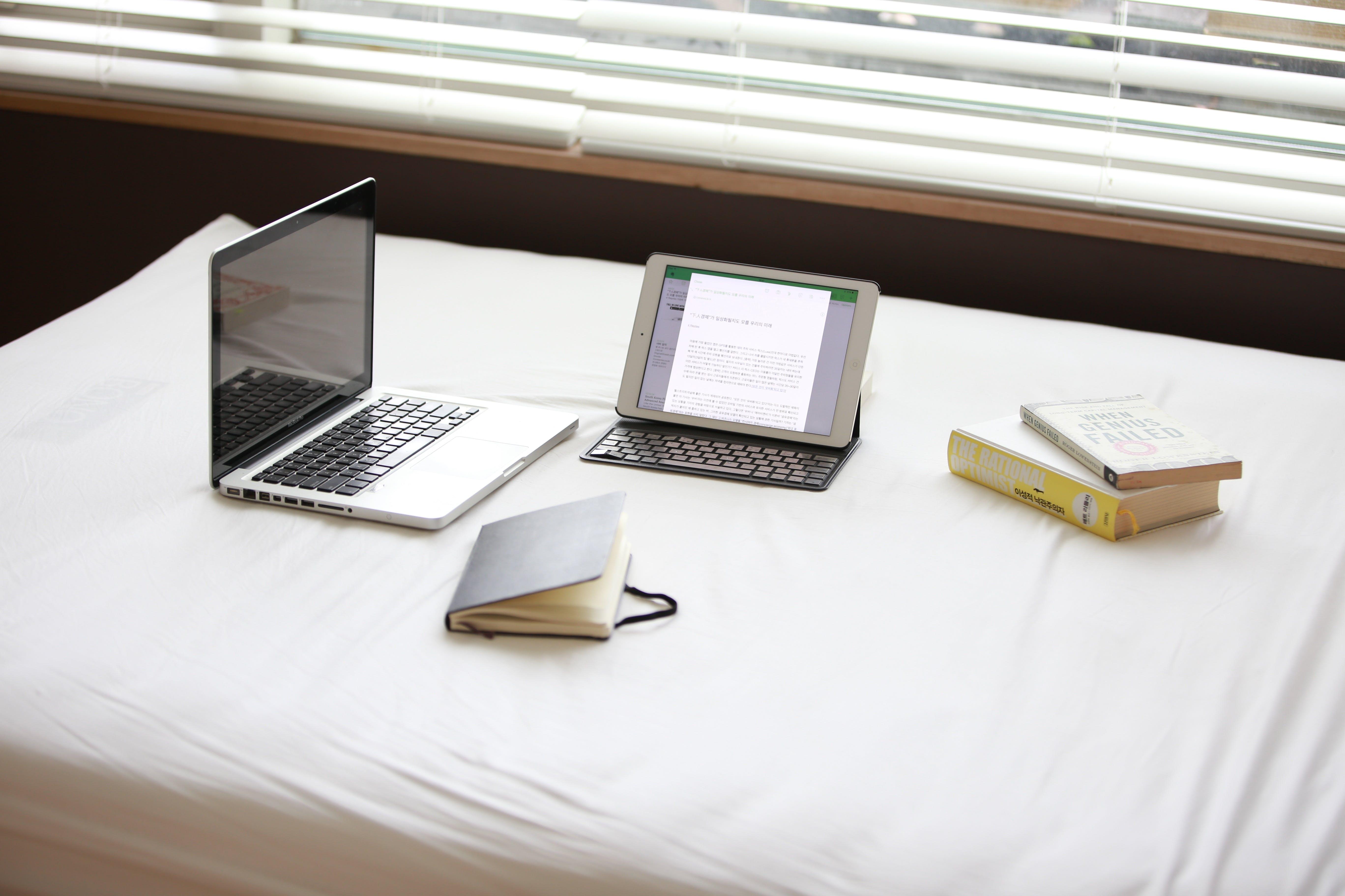 Macbook Pro over White Fabric Sheet Beside White Ipad