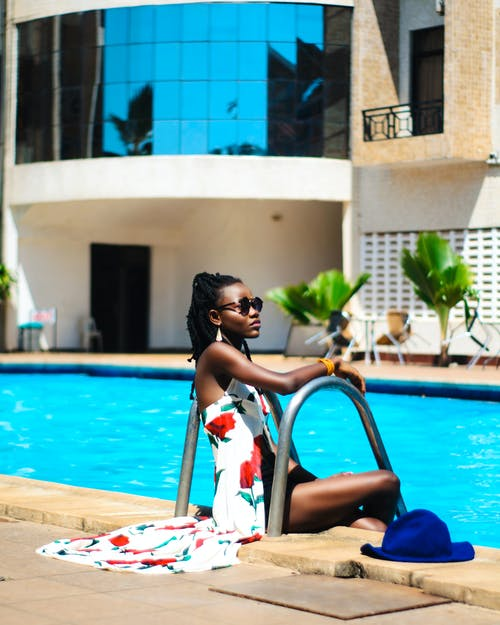 Woman Sitting Beside Swimming Pool