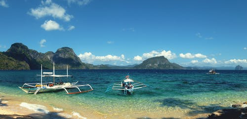 Free stock photo of beach, blue skies, blue water, fishing boats