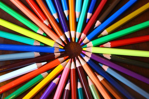 Assorted-color Pencils Forming Circle on Brown Surface
