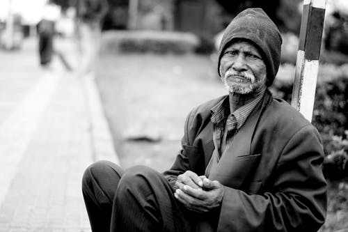 Grayscale Photography of Man Sitting
